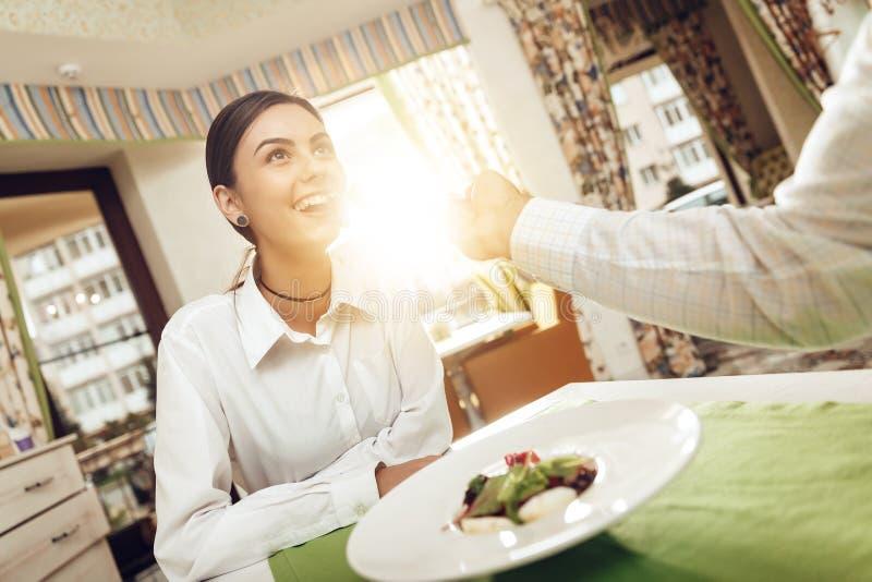 Ο ευτυχείς άνδρας και η γυναίκα έχουν το μεσημεριανό γεύμα σε ένα εστιατόριο στοκ φωτογραφία