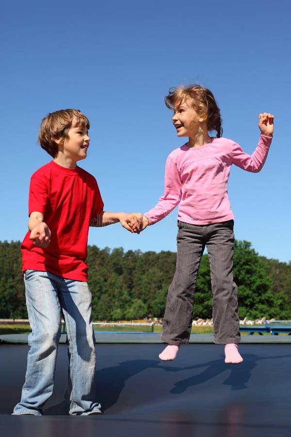 Ο ευτυχείς αδελφός και η αδελφή πηδούν στο τραμπολίνο στοκ φωτογραφία με δικαίωμα ελεύθερης χρήσης