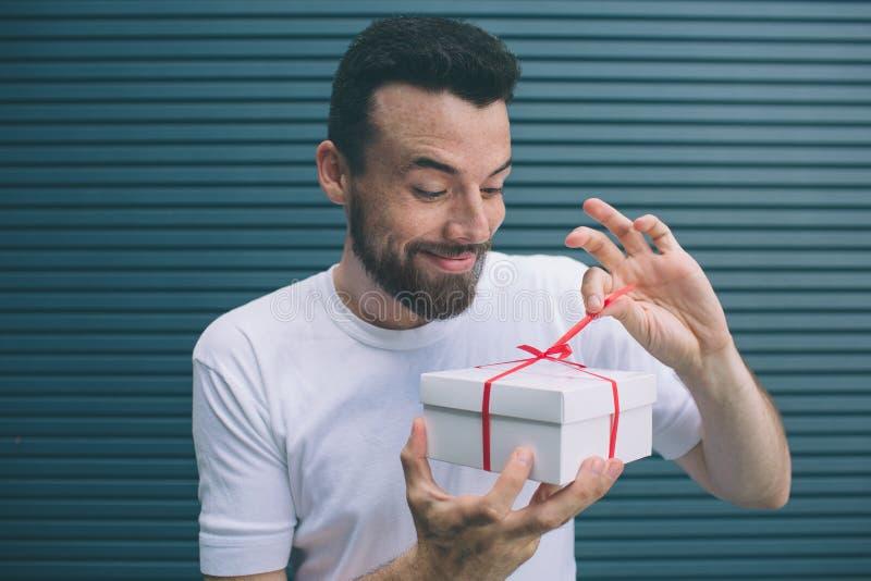 Ο ευχάριστος και συμπαθητικός τύπος ανοίγει το παρόν κιβώτιο Εξετάζει το irt και βγάζει την κόκκινη κορδέλλα Είναι πολύ συγκινημέ στοκ φωτογραφία με δικαίωμα ελεύθερης χρήσης