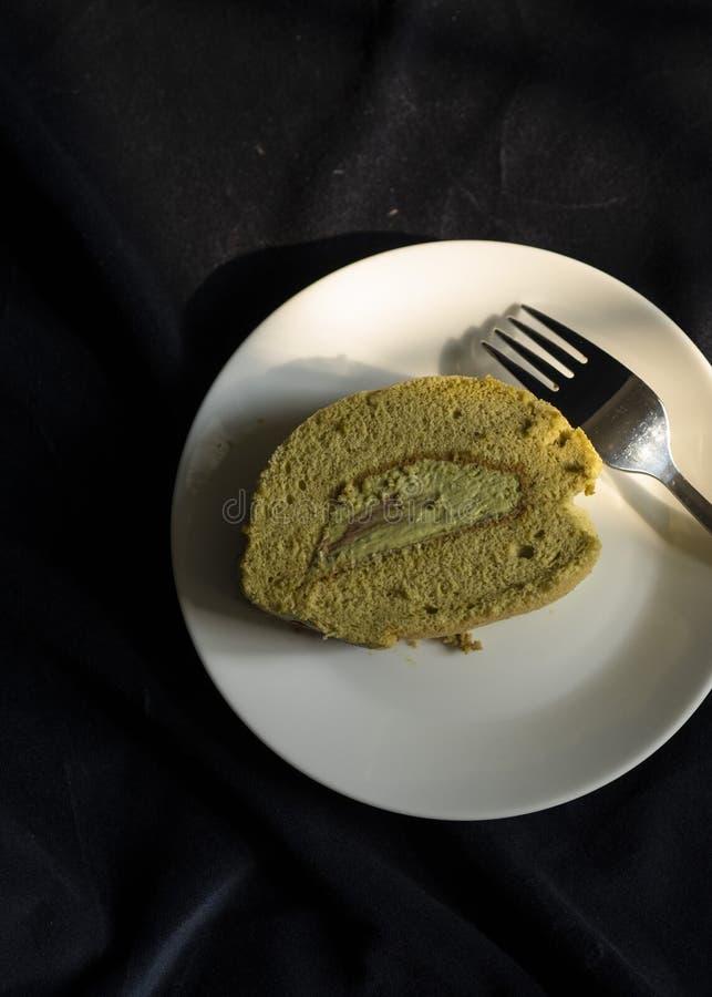 Ο εύγευστος ρόλος κέικ matcha στο πιάτο στοκ εικόνες