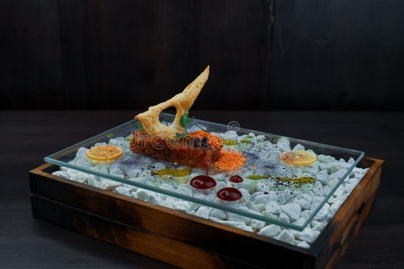 Ο εύγευστος τάρταρος των κόκκινων ψαριών με μια κροτίδα με μια σάλτσα σε έναν όμορφο πίνακα γυαλιού στέκεται σε έναν πίνακα σε έν στοκ εικόνες
