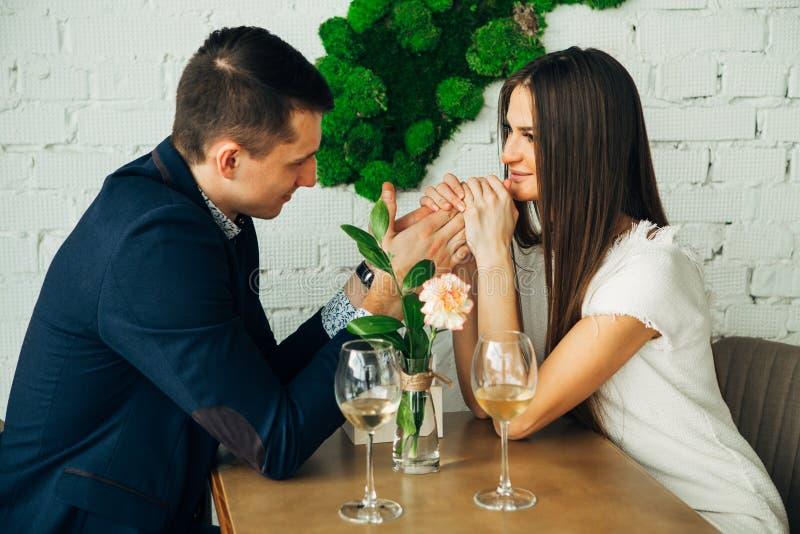 Ο εύθυμοι νεαρός άνδρας και η γυναίκα χρονολογούν στο εστιατόριο Κάθονται στον πίνακα και εξετάζουν ο ένας τον άλλον με την αγάπη στοκ φωτογραφία