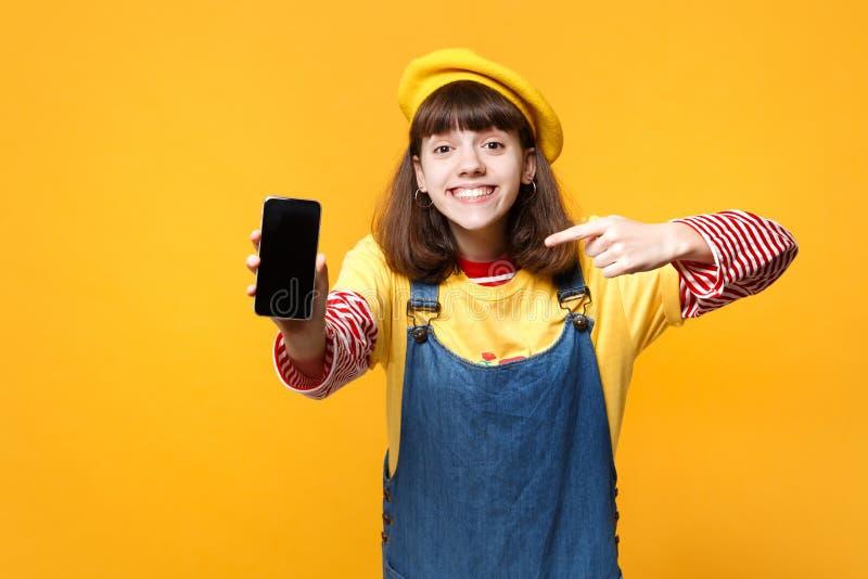 Ο εύθυμος έφηβος κοριτσιών γαλλικό beret που δείχνει το αντίχειρα στο κινητό τηλέφωνο με την κενή κενή οθόνη απομόνωσε σε κίτρινο στοκ φωτογραφία