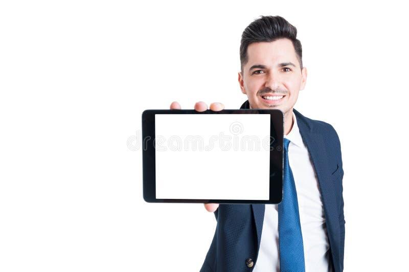 Ο εύθυμος επιχειρηματίας παρουσιάζει την οθόνη της σύγχρονης ταμπλέτας στοκ φωτογραφία