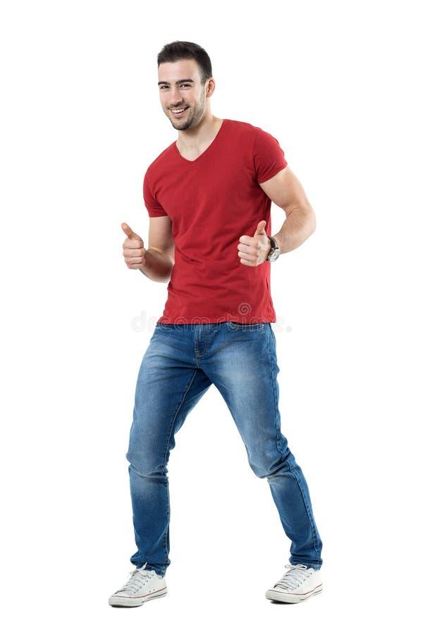 Ο εύθυμος συγκινημένος νεαρός άνδρας στην κόκκινη παρουσίαση μπλουζών φυλλομετρεί επάνω τη χειρονομία στοκ εικόνες