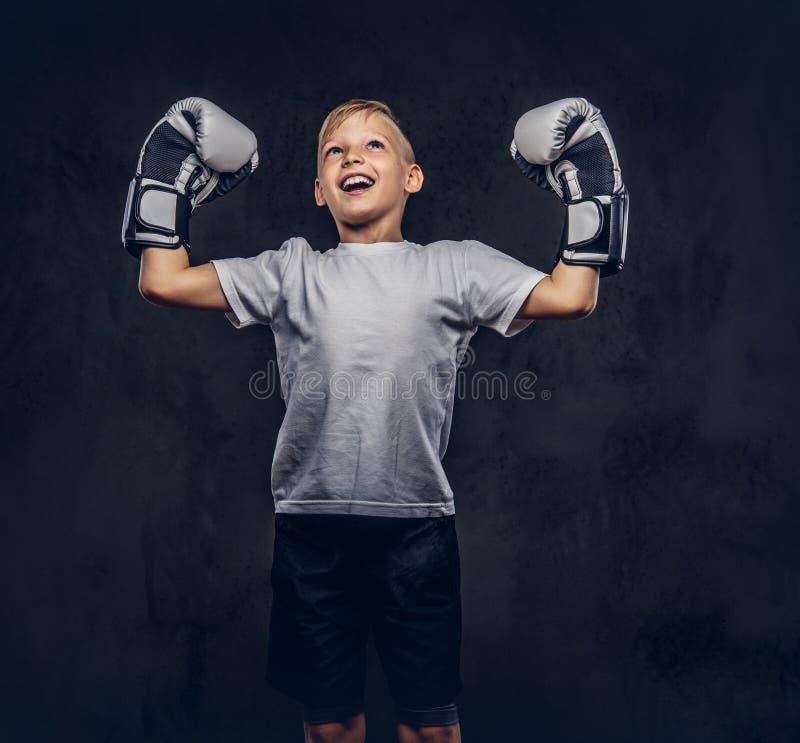 Ο εύθυμος όμορφος μπόξερ μικρών παιδιών με την ξανθή τρίχα που ντύνεται σε μια άσπρη μπλούζα που φορά τα εγκιβωτίζοντας γάντια χα στοκ εικόνα