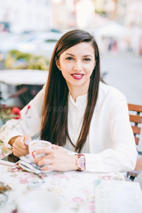 ο ελκυστικός καυκάσιος κινεζικός καφές καφέδων που πίνει το μικτό μοντέλο συναγωνίζεται υπαίθρια τη γυναίκα πεζοδρομίων στοκ εικόνα