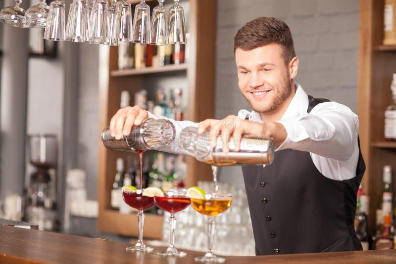 Ο ελκυστικός νέος μπάρμαν κάνει τα ποτά στο μπαρ στοκ εικόνα με δικαίωμα ελεύθερης χρήσης