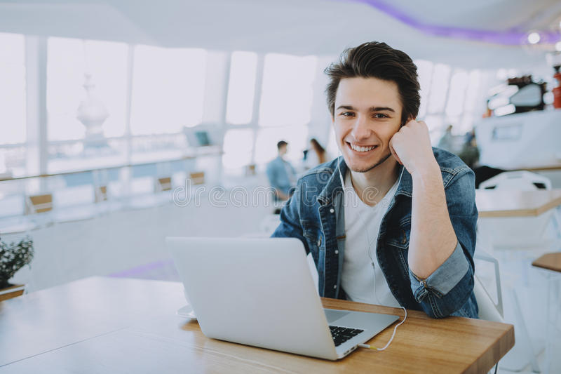 Ο ελκυστικός νεαρός άνδρας ή ανεξάρτητος κάθεται στον καφέ και χρησιμοποιεί κινητό του στοκ φωτογραφία με δικαίωμα ελεύθερης χρήσης