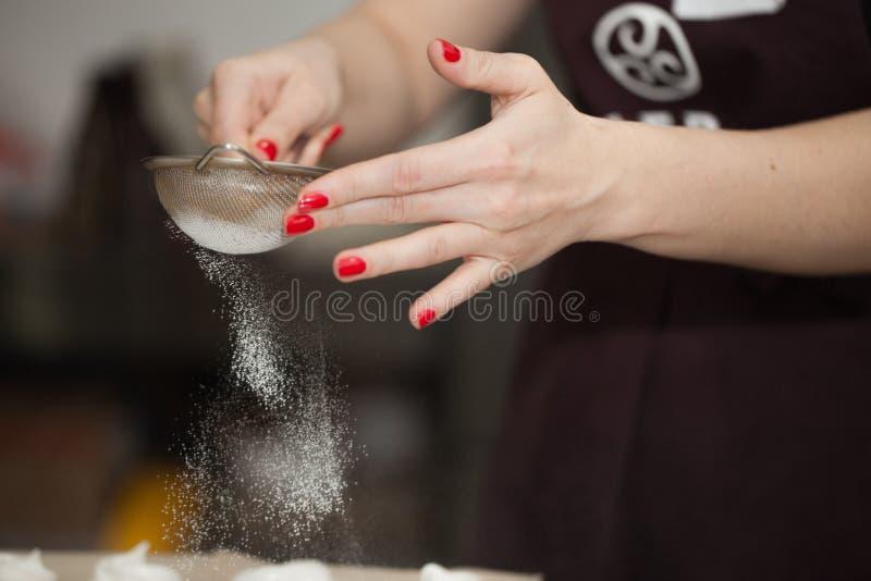 Ο ζαχαροπλάστης ψεκάζει την κονιοποιημένη ζάχαρη στοκ φωτογραφίες με δικαίωμα ελεύθερης χρήσης