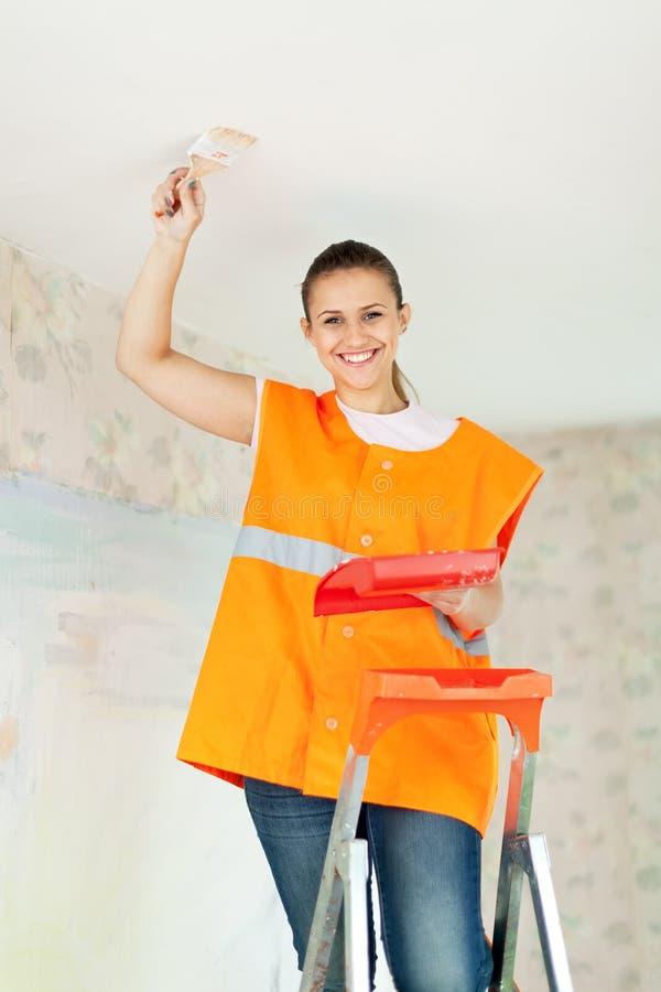 Ο ζωγράφος σπιτιών θηλυκών χρωματίζει το ανώτατο όριο στοκ εικόνα