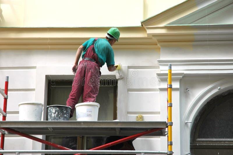 Ο ζωγράφος σπιτιών πίσω από την εργασία. στοκ φωτογραφία