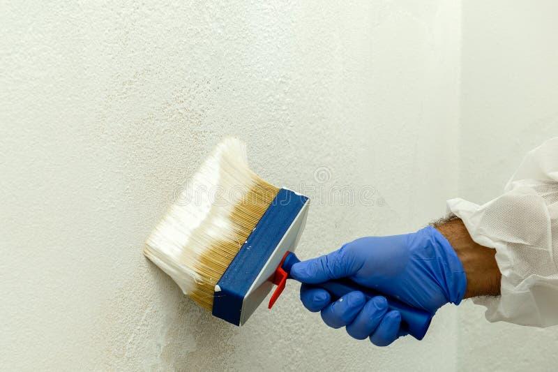 Ο ζωγράφος χρωματίζει τον τοίχο με την απόχρωση του λευκού στοκ φωτογραφία με δικαίωμα ελεύθερης χρήσης