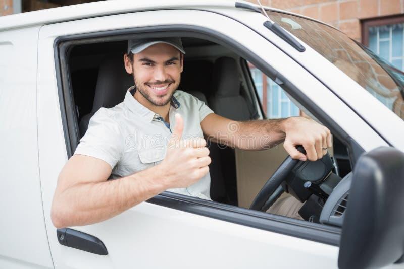Οδηγός παράδοσης που παρουσιάζει αντίχειρες που οδηγούν επάνω το φορτηγό του στοκ φωτογραφίες