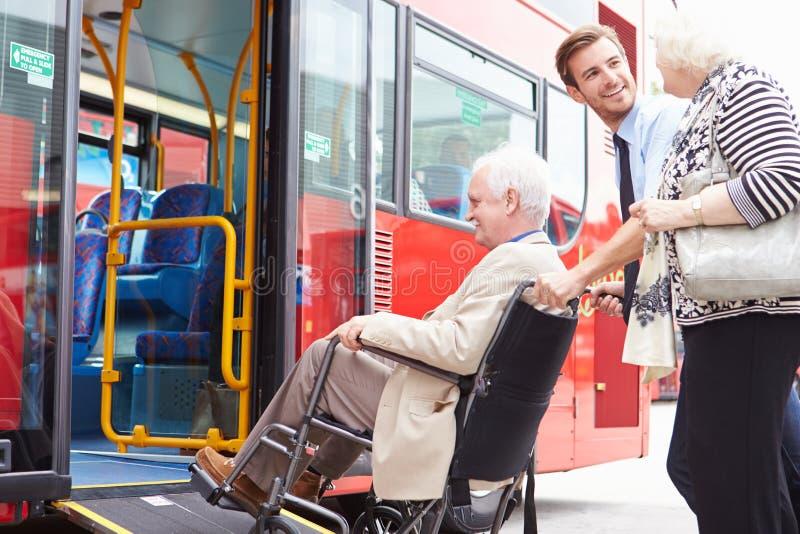 Οδηγός που βοηθά το ανώτερο λεωφορείο πινάκων ζεύγους μέσω της κεκλιμένης ράμπας αναπηρικών καρεκλών στοκ εικόνα