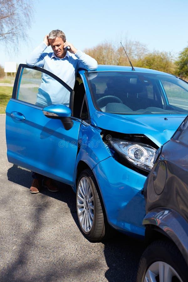 Οδηγός που κάνει το τηλεφώνημα μετά από το τροχαίο ατύχημα στοκ εικόνα με δικαίωμα ελεύθερης χρήσης