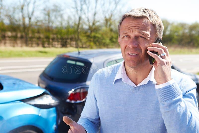 Οδηγός που κάνει το τηλεφώνημα μετά από το τροχαίο ατύχημα στοκ φωτογραφία με δικαίωμα ελεύθερης χρήσης