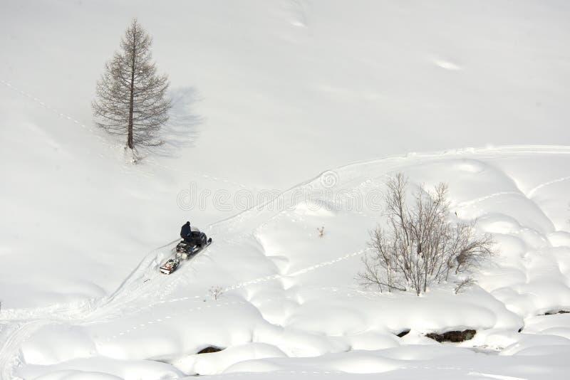 Οδηγώντας αθλητικό όχημα για το χιόνι ατόμων σε μια ηλιόλουστη ημέρα στοκ εικόνα με δικαίωμα ελεύθερης χρήσης