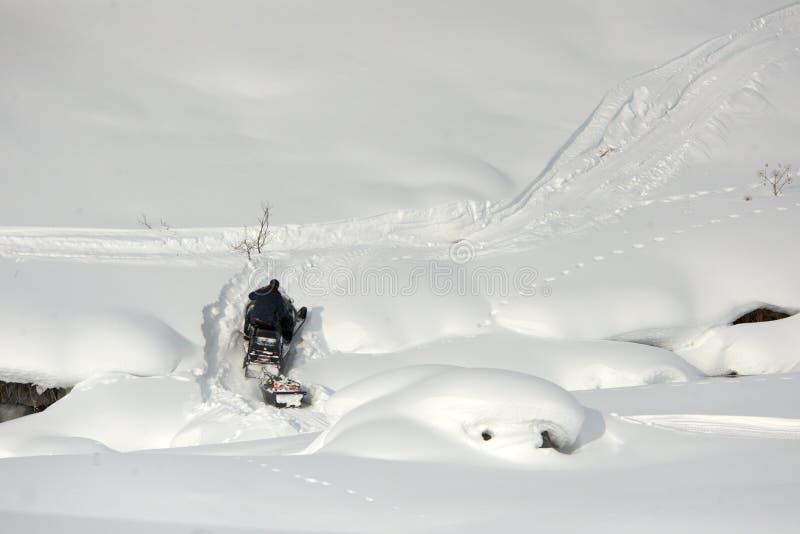 Οδηγώντας αθλητικό όχημα για το χιόνι ατόμων σε μια ηλιόλουστη ημέρα στοκ φωτογραφία με δικαίωμα ελεύθερης χρήσης