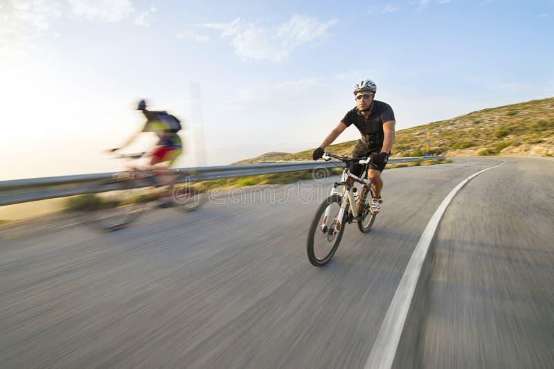 Οδηγώντας ποδήλατο βουνών ατόμων ποδηλατών στην ηλιόλουστη ημέρα στοκ εικόνα με δικαίωμα ελεύθερης χρήσης