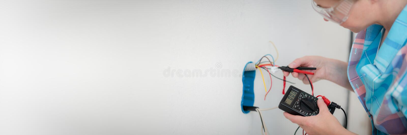 Ο ηλεκτρολόγος γυναικών χρησιμοποιεί τον ψηφιακό μετρητή για να μετρήσει την τάση στην έξοδο ισχύος στοκ φωτογραφία