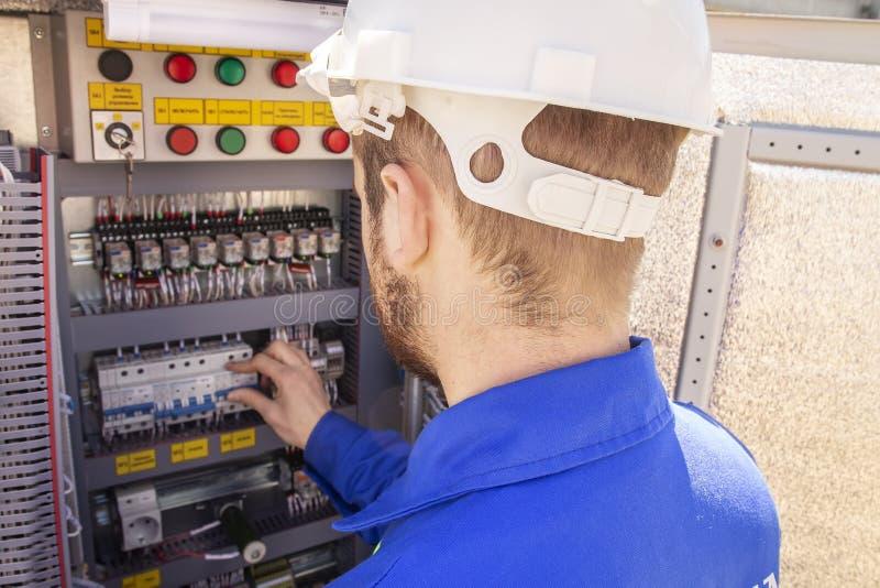 Ο ηλεκτρολόγος ρυθμίζει το ηλεκτρικό γραφείο ο μηχανικός στο κράνος εξετάζει τον ηλεκτρικό εξοπλισμό στοκ εικόνες