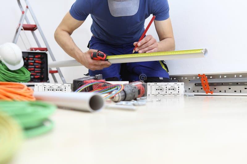 Ο ηλεκτρολόγος στην εργασία με το μετρητή και το μολύβι στα χέρια μετρά τον πλαστικό σωλήνα για να περάσει τα ηλεκτρικά καλώδια σ στοκ εικόνα