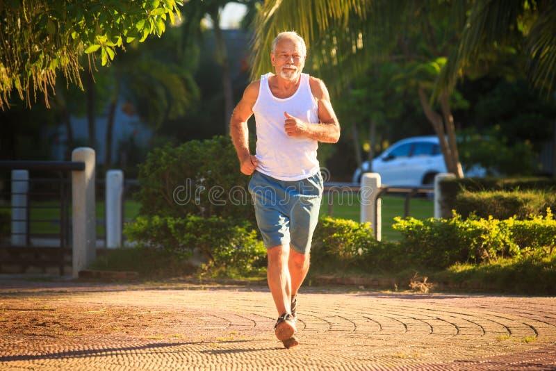Ο ηληκιωμένος κάνει τα τρεξίματα ασκήσεων πρωινού κατά μήκος του πάρκου στοκ φωτογραφία