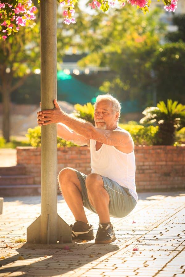 Ο ηληκιωμένος κάνει τις στάσεις οκλαδόν ασκήσεων πρωινού από Πολωνό στο πάρκο στοκ φωτογραφία