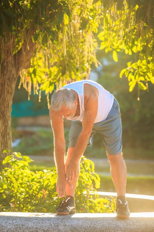 Ο ηληκιωμένος κάνει το σώμα κάμψεων ασκήσεων πρωινού στο πόδι στο εμπόδιο στοκ εικόνες με δικαίωμα ελεύθερης χρήσης