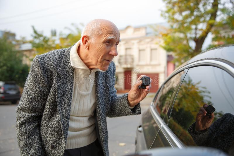 Ο ηληκιωμένος κρατά μια κάμερα δράσης και κοιτάζει στο βαμμένο παράθυρο του αυτοκινήτου Υπαίθρια στην οδό στοκ εικόνες