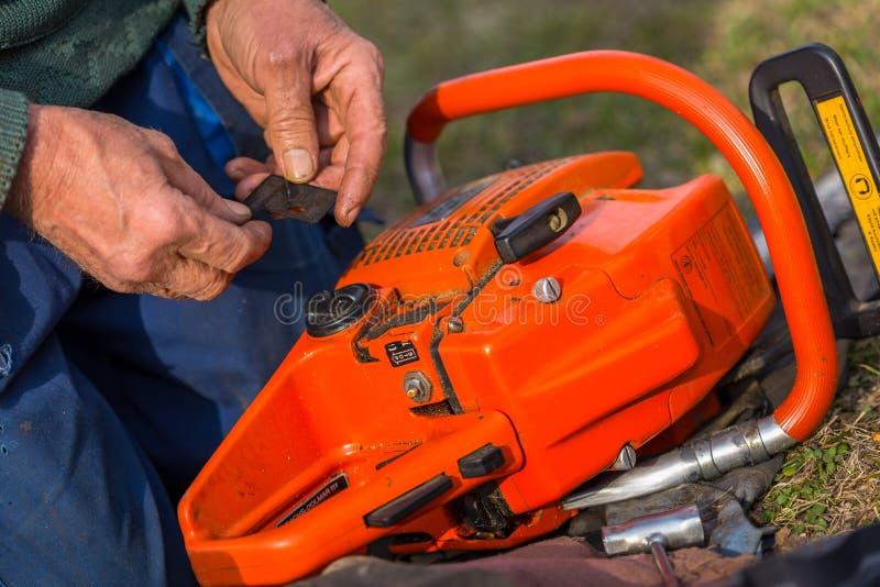 Ο ηληκιωμένος στα μπλε εσώρουχα επισκευάζει το πορτοκαλί αλυσιδοπρίονο που τοποθετείται στο έδαφος με τα γυμνά χέρια του στοκ φωτογραφία με δικαίωμα ελεύθερης χρήσης