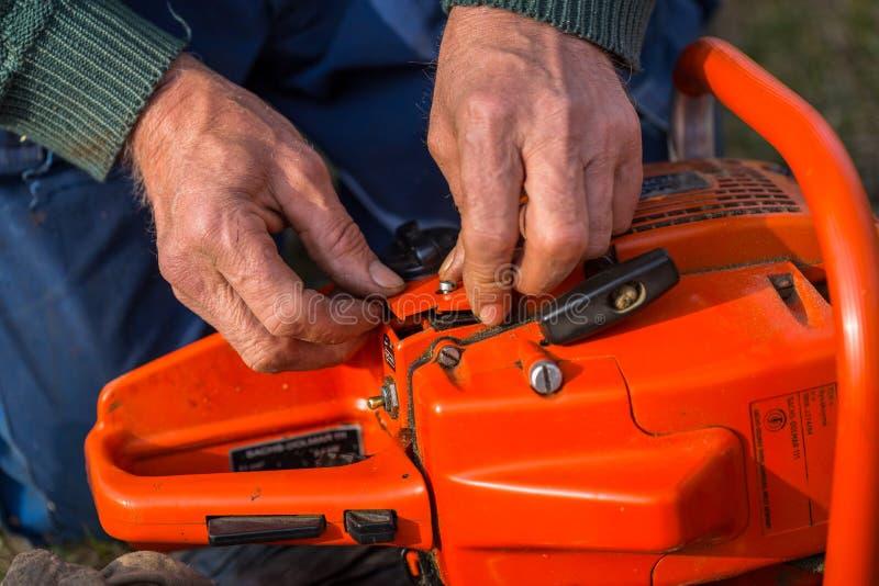 Ο ηληκιωμένος στα μπλε εσώρουχα επισκευάζει το πορτοκαλί αλυσιδοπρίονο που τοποθετείται στο έδαφος με τα γυμνά χέρια του στοκ εικόνες