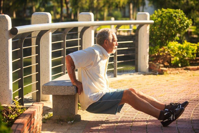 Ο ηληκιωμένος στο άσπρο πουκάμισο κάνει τις ασκήσεις πρωινού από τον πάγκο στο πάρκο στοκ εικόνες