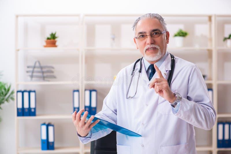 Ο ηλικίας αρσενικός γιατρός που εργάζεται στην κλινική στοκ εικόνες