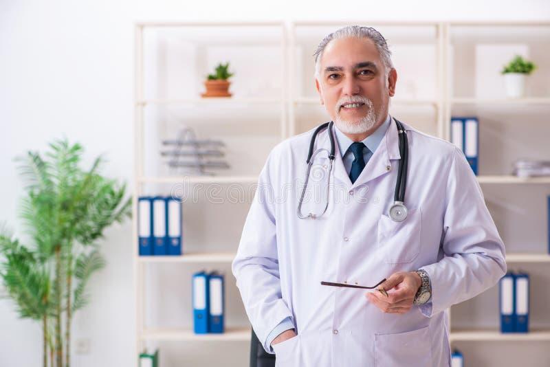 Ο ηλικίας αρσενικός γιατρός που εργάζεται στην κλινική στοκ εικόνα με δικαίωμα ελεύθερης χρήσης