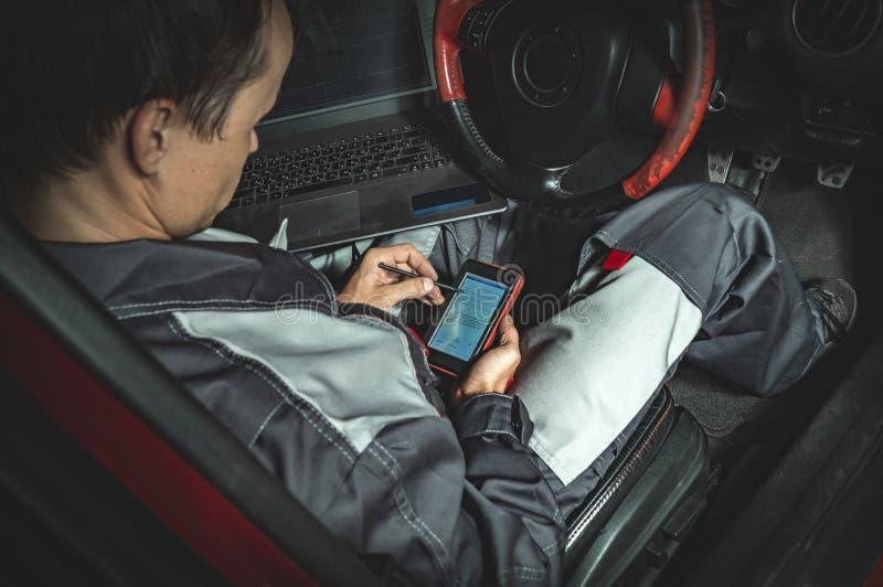 Ο ηλεκτρολόγος παράγει μια μηχανή αυτοκινήτων κωδίκων λάθους ανάγνωσης στοκ εικόνα
