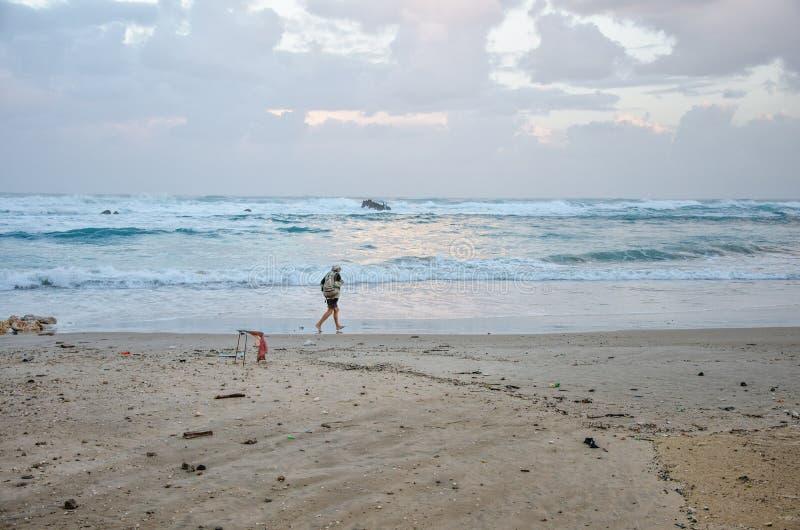 Ο ηληκιωμένος περπατά γρήγορα στη χειμερινή θυελλώδη παραλία στοκ εικόνες με δικαίωμα ελεύθερης χρήσης