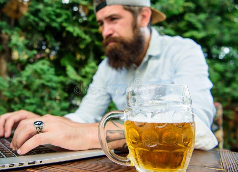 Ο θαυμαστής στοιχημάτισε το σε απευθείας σύνδεση πρωτάθλημα ενώ καθίστε το πεζούλι υπαίθρια με την μπύρα Το γενειοφόρο hipster οπ στοκ φωτογραφίες με δικαίωμα ελεύθερης χρήσης