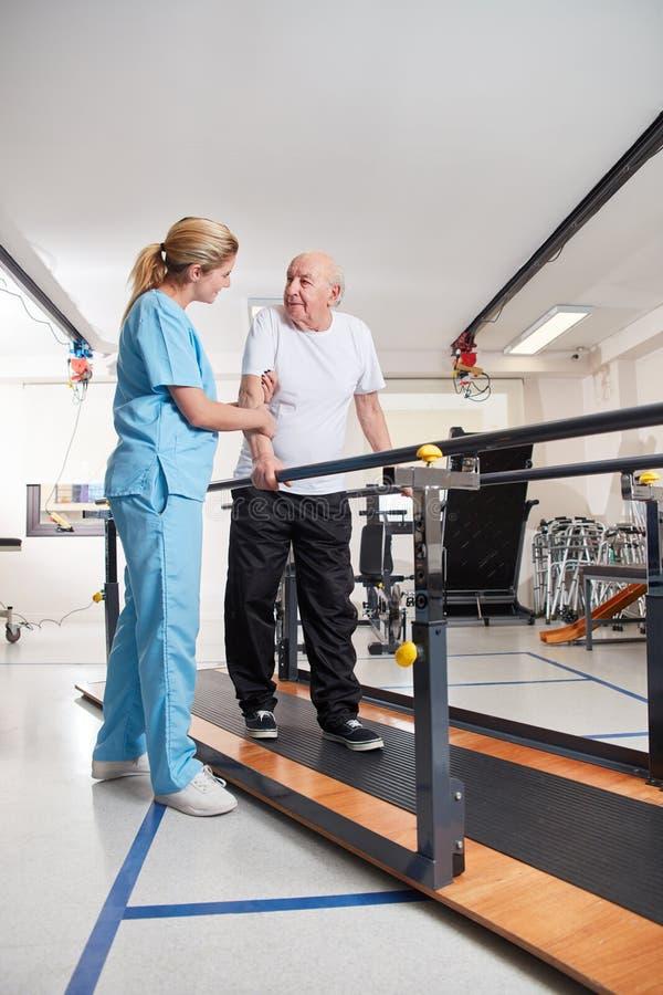 Ο θεράπων υποστηρίζει το ανώτερο άτομο treadmill στοκ εικόνα