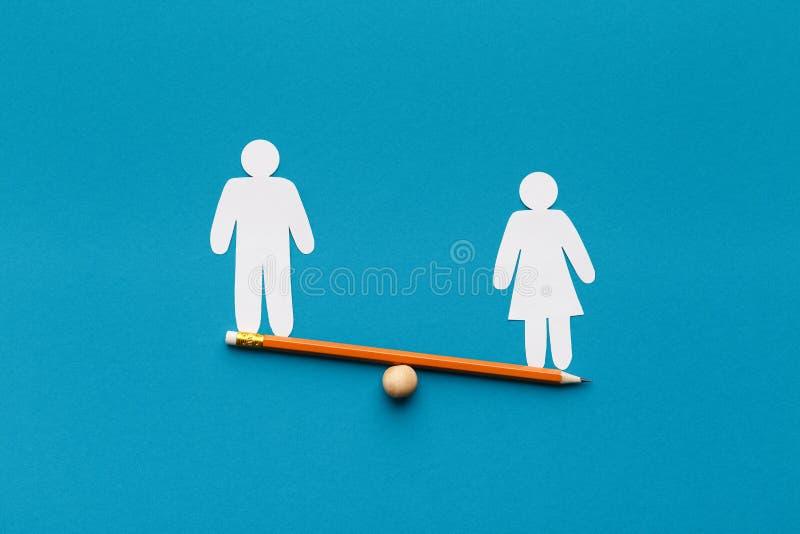Ο θηλυκός αριθμός ξεπερνά το αρσενικό seesaw, μπλε υπόβαθρο σε βάρος στοκ εικόνες με δικαίωμα ελεύθερης χρήσης