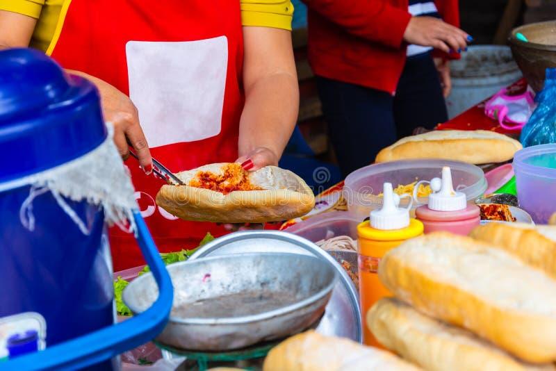 Ο θηλυκός αρχιμάγειρας που κάνει το baguette ύφους του Λάος ή γαλλικά πασπαλίζει με ψίχουλα sanwich, ιδιαίτερα δημοφιλή τρόφιμα ο στοκ εικόνες