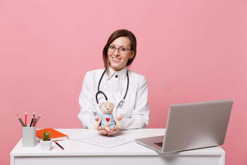 Ο θηλυκός γιατρός κάθεται στην εργασία γραφείων για τον υπολογιστή με το ιατρικό παιχνίδι λαβής εγγράφων στο νοσοκομείο που απομο στοκ εικόνες