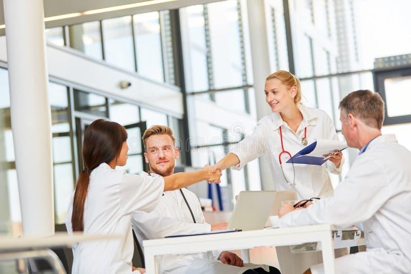 Ο θηλυκός γιατρός καλωσορίζει τους συναδέλφους στην ομάδα με τη χειραψία στοκ εικόνες