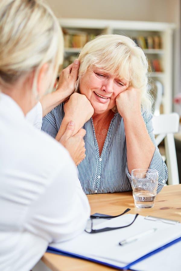 Ο θηλυκός γιατρός παρηγορεί το φωνάζοντας ασθενή σε ραντεβού στοκ εικόνα