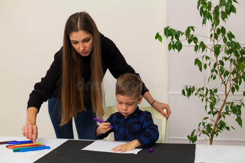 Ο θηλυκός δάσκαλος διδάσκει ένα μικρό αγόρι για να σύρει στον πίνακα στοκ εικόνες με δικαίωμα ελεύθερης χρήσης