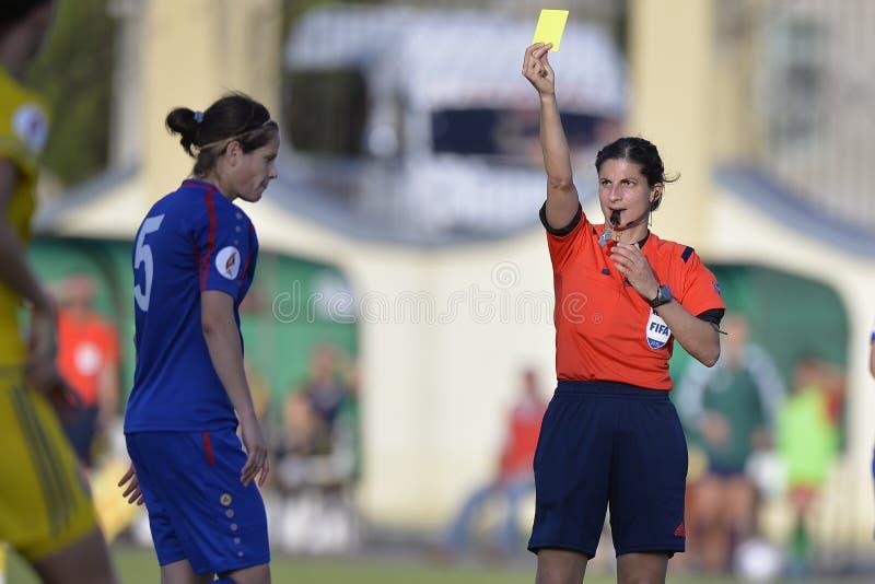Ο θηλυκός διαιτητής ποδοσφαίρου, Riem Χουσεΐν παρουσιάζει κίτρινη κάρτα στοκ εικόνες