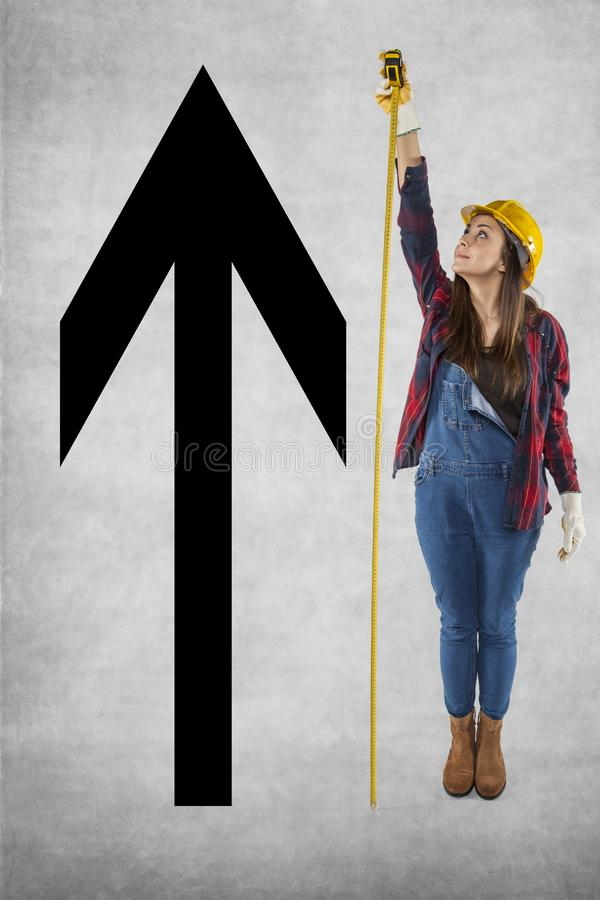 Ο θηλυκός εργάτης οικοδομών μετρά ένα πολύ υψηλό βέλος στοκ εικόνες