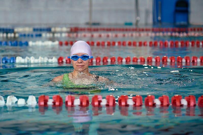 Ο θηλυκός κολυμβητής προκύπτει από το νερό Τελείωσε κολυμπά στη λίμνη στοκ εικόνες