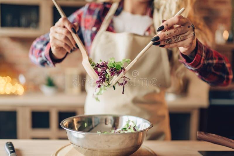 Ο θηλυκός μάγειρας στην ποδιά προετοιμάζει τη φρέσκια σαλάτα στοκ εικόνες με δικαίωμα ελεύθερης χρήσης